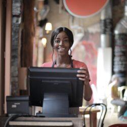 cheerful black waitress standing at counter[:]