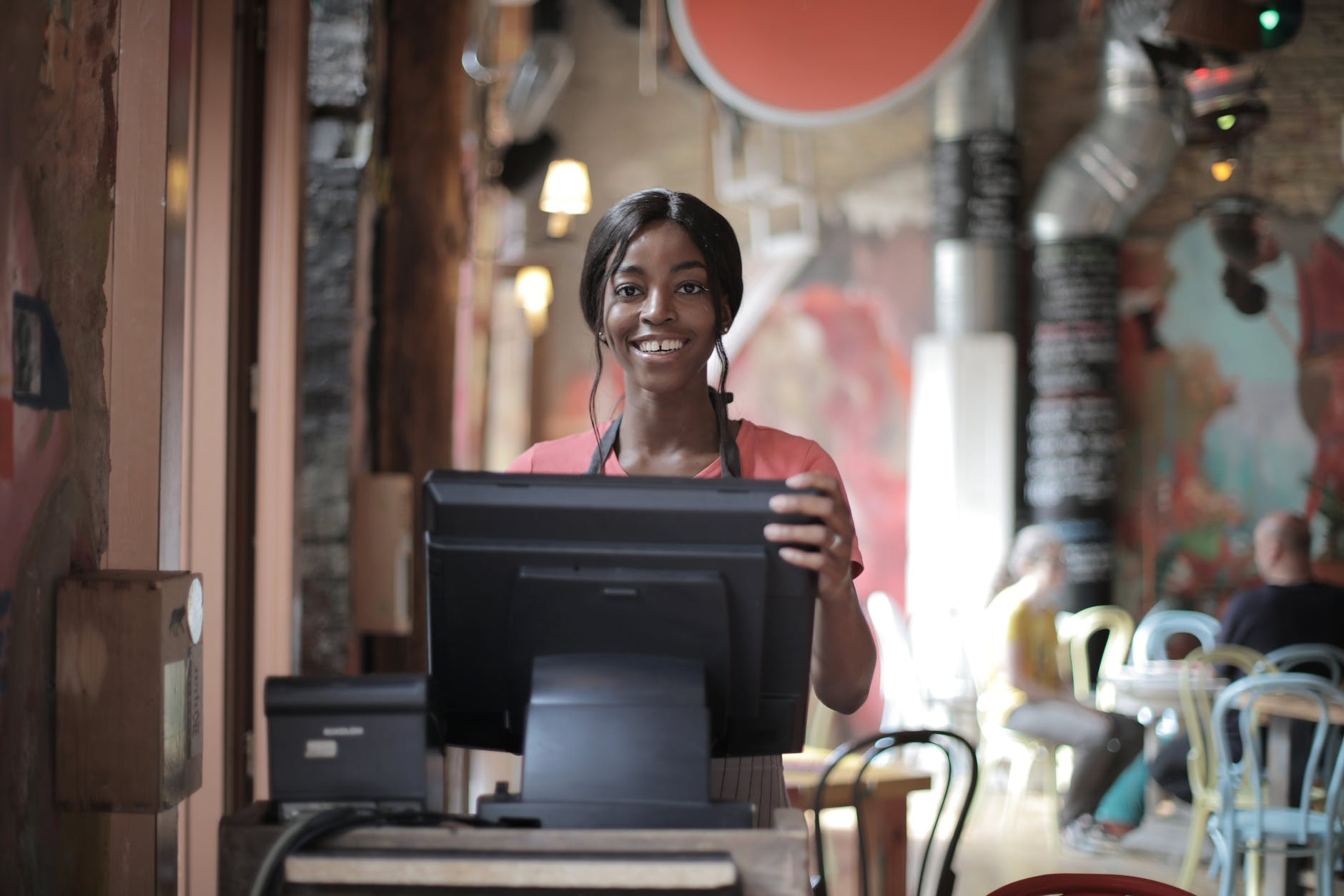 cheerful black waitress standing at counter[:]