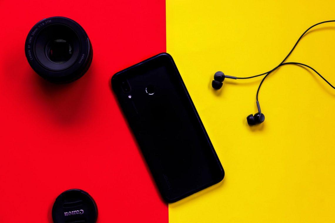 black smartphone besides earphones and camera lens