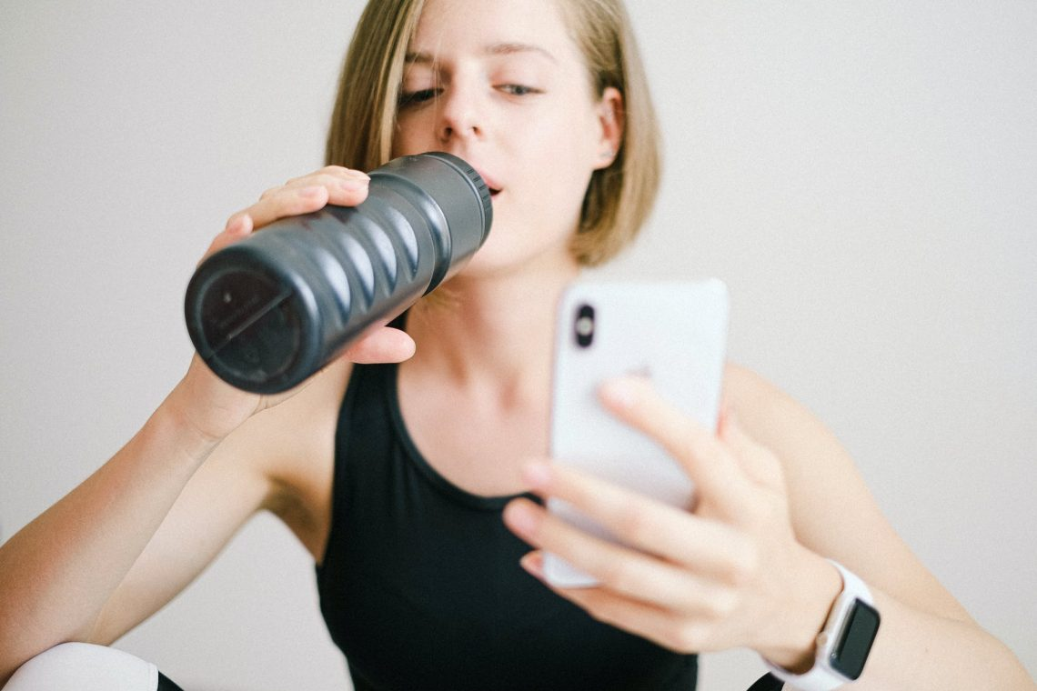 woman in black tank top holding white smartphone while drinking